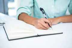 Close up view of a businesswoman writing notes Stock Image