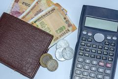 Close up view of calculator, wallet with brand new Indian 200 rupees banknotes and 1,2,10 rupee coins on white background royalty free stock photos
