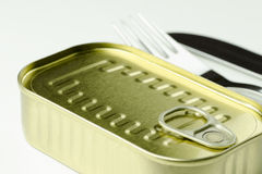 Close-up view of a can of food with a fork and a knife on a whit. E background Royalty Free Stock Photos