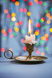 Close up view on candle in candlestick on blue table and backgro Stock Photos
