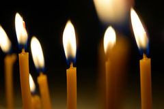 Close up view of the candles burning brightly in the dark. Royalty Free Stock Photos