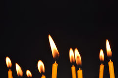 Close up view of the candles burning brightly in the dark. Stock Photo
