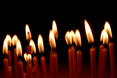 Close up view of the candles burning brightly in the dark. Stock Image