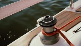 Close-up view of capstan head shining in the sun. Rope fixing around capstan drum, the crew steers the ship. stock footage