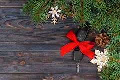 Close-up view of car keys with red bow as present on wooden background.  Stock Photo