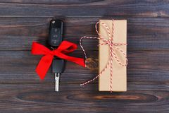 Close-up view of car keys with red bow as present on wooden background stock images