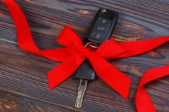 Close-up view of car keys with red bow as present on wooden background Stock Photo