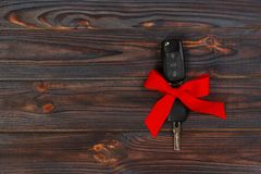 Close-up view of car keys with red bow as present on wooden background.  Royalty Free Stock Photography
