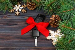 Close-up view of car keys with red bow as present on wooden background.  Royalty Free Stock Images