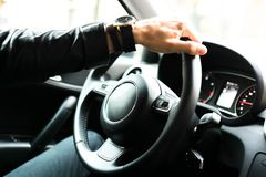 Hands on car steering wheel. Close up view of a car steering wheel. Manual gearbox. Car interior details. Car transmission. Soft lighting. Abstract view Stock Images