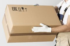 Close-up view of cardboard box in mover hands. Relocation services man in uniform with cardboard box. stock images