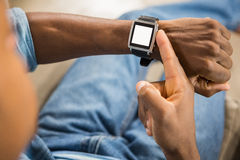 Close up view of a casual man using smart watch. In living room Stock Photo