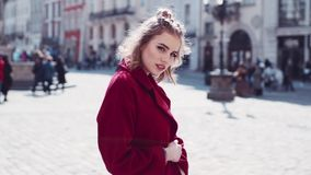 Close up view of charming young lady playfully looking towards the camera in the city center. Modern times, stylish stock video