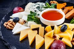 Close up view on cheese plate served with nuts, grapes, honey. Selective focus on different types of cheese on dark background royalty free stock photo