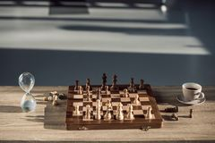 Close-up view of chess board with pieces, cup of coffee and sand clock. On table Royalty Free Stock Images