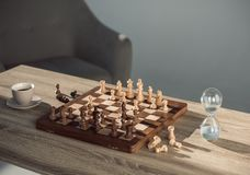Close-up view of chess board with pieces, cup of coffee and sand clock. On table royalty free stock photography