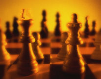 Close up view of chess board showing king and queen in foreground Royalty Free Stock Images