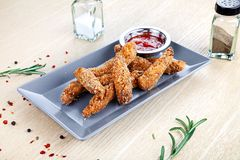 Close up view on Chicken strips breaded deep-fried with ketchup on white table royalty free stock image