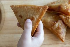 A close up view of a child holding a samosa stock photo