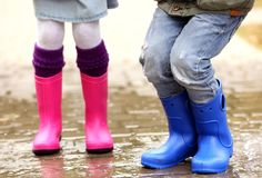 Close up view of children legs in gumboots jumping. On wet pavement Stock Images