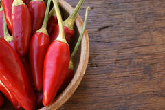Close up view of chili pods in a bowl. Close up view of fresh chili pods in a wooden bowl on a rustic wooden tabke with copy space Stock Photos