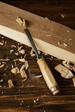Close up view of chisel and wooden pieces on brown table stock images