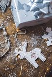 Close up of Christmas decorations, silver wrapped Christmas gift and decorations on a wooden background royalty free stock photo