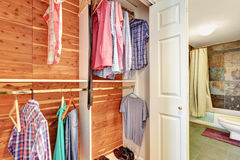 Close-up view of clothes and shirts on wooden hangars in a closet. Close-up view of clothes and shirts on wooden hangars in a closet with white sliding doors royalty free stock photos