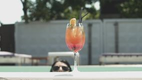 Close-up view of a cocktail standing on the edge of a swimming pool in the background of splashing water with shiny. Sparkles stock video