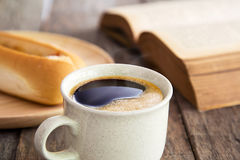 Close up view of coffee cup with bread and books on old wood flo Royalty Free Stock Photography