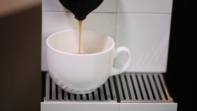 Close up view of coffee running from the capsule coffe machine into white cup. Beautiful backgrounds stock video