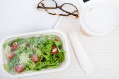 Close up view coffee to go, take away food and eyeglasses. On table royalty free stock images