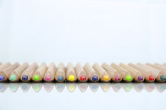 Close-up view of colored pencils lying on glossy white background with reflection isolated Stock Image