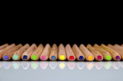 Close-up view of colored pencils lying on glossy white background with reflection isolated Royalty Free Stock Image