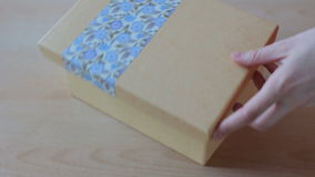Close up view of colorful gift box. Hands put a greeting card into box and close it stock video footage
