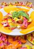Close up view of colorful ravioli pasta in a plate with pesto sauce and basil Royalty Free Stock Photography