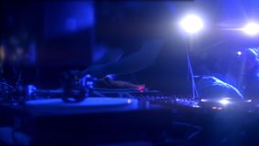 Close up view of the colourful controls on the deck at night with the hands of a DJ mixing and scratching music at a stock footage