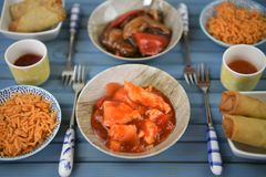Close up side view of a dinner table with small dishes of Chinese food. A close up view of the cooked and served chicken and rice dishes and a small yellow pot Royalty Free Stock Images