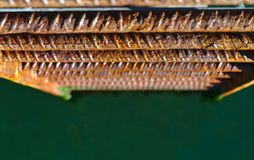 Close up view of corrosive metal ladder. With green water blurred in background stock photography