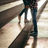 Close-up view of the couple legs during the sunset. The female ones are standing on the stairs while the male hand is. Touching them Royalty Free Stock Images