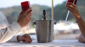 Close-up view of the couple of lovers clinking glasses with wine and drinking in restaurant. No face. Close-up view of the couple of lovers clinking glasses stock footage