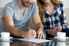 Tenants write signature on rental sale agreement, close up view. Close up view of couple signing documents, customers renters tenants or clients write signature royalty free stock image