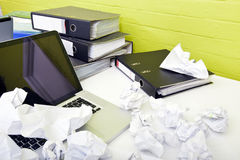 Close-up view of crumpled paper over laptop on desk with empty chair and folders Royalty Free Stock Photography