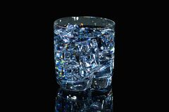 Close up view of crystal glass with water and ice cubes. stock photos