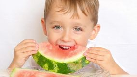 Close-up view of cute little boy sitting at the table on the kitchen. Male holding a piece and eating a watermelon - 1. Royalty Free Stock Photos