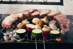 Delicious meat with vegetables preparing on grill stock photo