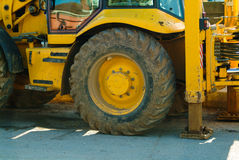 Close-up view of a dirty wheel of yellow heavy earth mover Stock Photos