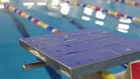 Close-up view of diving board in swimming pool. A blue springboard for jumping into the water in the pool stock video