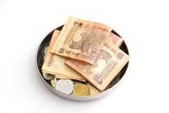 Donation plate with indian banknotes and coins on white background. Close up view of donation plate with indian banknotes and coins on white background stock images