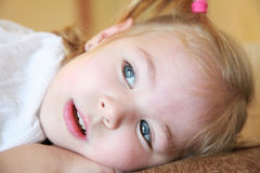 Close up view of a dreaming little girl with blue eyes laying down Stock Photography